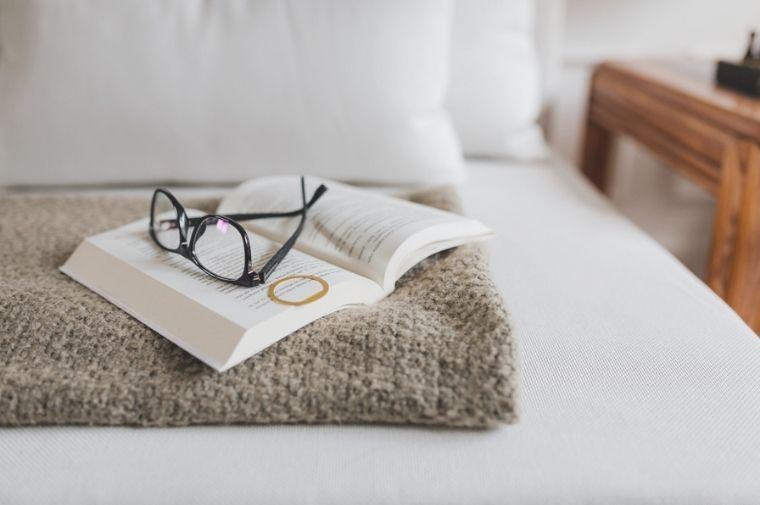 ベットの上にある本とメガネ