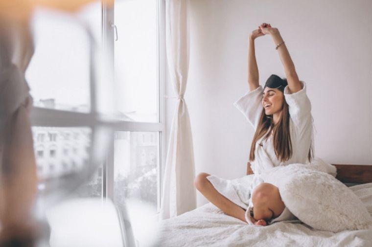 朝日を浴びて伸びをしている女性