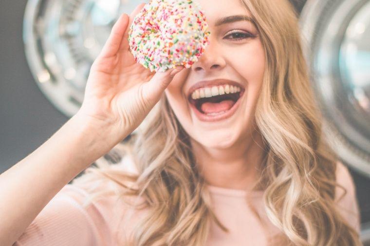 ドーナツを持っている笑顔の女性