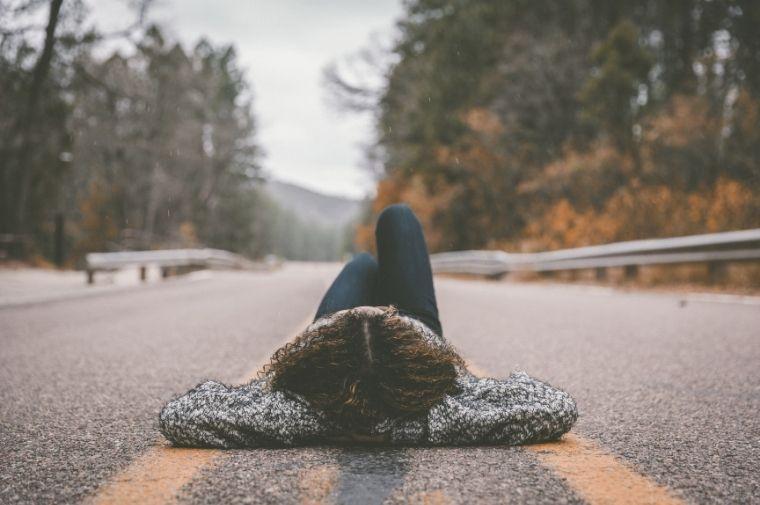 道路で寝転がって考えている女性
